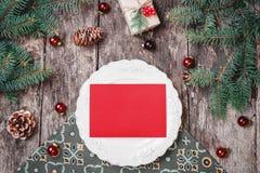 Julplattan med inbjudan på träferiebakgrund med gåvan, sörjer kottar, röda garneringar, granfilialer royaltyfri foto