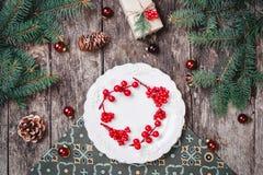 Julplattan med julkransen på träbakgrund med gåvan, sörjer kottar, röda garneringar arkivbilder