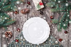 Julplattan på träferiebakgrund med gåvan, sörjer kottar, röda garneringar, granfilialer royaltyfri fotografi