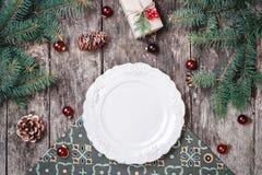 Julplattan på träferiebakgrund med gåvan, sörjer kottar, röda garneringar, granfilialer fotografering för bildbyråer
