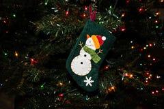 Julprydnad av en snögubbe på en strumpa på ett vintergrönt träd royaltyfri foto