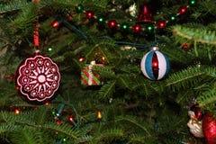 Julprydnader som glöder på ett grönt, sörjer träd 2 Arkivbild