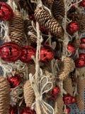 Julpynt girlander, sörjer kottar och röda klirr royaltyfri foto