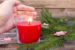 Julpynt, granfilialer och kantjusterad hand som rymmer den röda flammande stearinljuset på tappningträbrädebakgrund arkivfoton