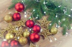 Julpynt med granfilialer på träbakgrund, bollar och stjärnor, guld- och rött royaltyfri fotografi