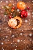 Julpynt med granträdfilialen och tangerin på träbakgrund med snö som är suddig arkivfoto