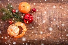 Julpynt med granträdfilialen och tangerin på träbakgrund med snö som är suddig royaltyfria bilder