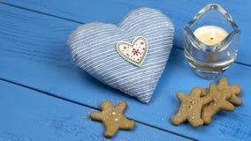 Julpynt på en blå tabell: kakor stearinljus, hjärtaleksak royaltyfri foto