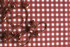 Julpynt: röd klockagirland på röd och vit rutig bakgrund royaltyfri fotografi
