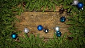 Julpynt som faller på en träbakgrund med granfilialer och kottar som är klara för din design vinter för snow för pojkeferielay
