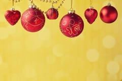 Julpynt som hänger över guld- bokehbakgrund med kopieringsutrymme arkivbild