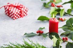 Julpynt-, stearinljus- och järneksidor med röda bär arkivbilder
