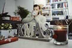 Julpyntgåvor och stearinljus hemma var en ung man sitter på soffan som dricker den varma drinken bara royaltyfri fotografi