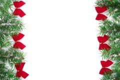 Julram av granträdfilialen med snö och röda pilbågar som isoleras på vit bakgrund med kopieringsutrymme för din text Arkivbilder