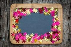 Julram av konfettier på svart tavla Arkivfoton