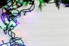 Julramen av girlandljus på gran förgrena sig stilfull borde Arkivbild