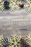 Julsörjer träbakgrund med dekorativa snöflingor och kottar Arkivbilder