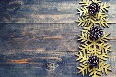 Julsörjer träbakgrund med dekorativa snöflingor och kottar Royaltyfri Fotografi