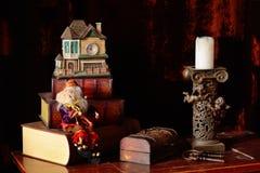 Julsammansättning av böcker, en bröstkorg med tangenter, stearinljus på a royaltyfri fotografi
