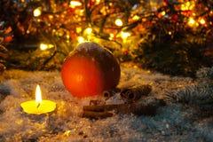 Julsammansättning av stearinljus, apelsinen och kanelbruna pinnar Royaltyfria Bilder