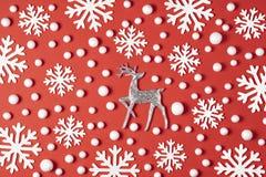 Julsammansättning gjorde av vita snöflingor, hjortar på röd bakgrund Begrepp för vinter för nytt år minsta Lekmanna- lägenhet royaltyfria bilder
