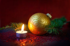 Julsammansättning - guld- boll, prydlig filial och en brinnande stearinljus Fotografering för Bildbyråer