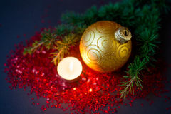 Julsammansättning - guld- boll, prydlig filial och en brinnande stearinljus Royaltyfri Fotografi
