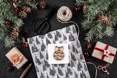 Julsammansättning med bokstaven, xmas som slår in, granfilialer, gåvor, sörjer kottar, röda garneringar, sax på feriebakgrund arkivfoton