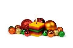 Julsammansättning med bränningstearinljuset och färgade bollar royaltyfria foton