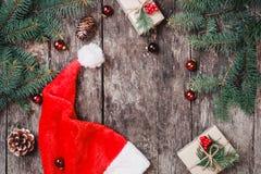 Julsammansättning med den röda jultomtenhatten, granfilialer, sörjer kottar, röda garneringar på träbakgrund arkivfoto