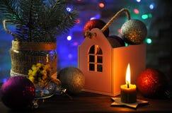 Julsammansättning med en brinnande stearinljus, ett hus och julpynt på en tabell arkivbilder