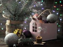 Julsammansättning med en stearinljus, ett hus och julpynt på en tabell royaltyfri bild