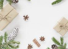 Julsammansättning med gåvaaskar som slås in i kraft papper, gran förgrena sig med kotten royaltyfri bild