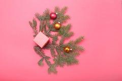 Julsammansättning med gåvaasken och ljus, röda bollar på trätabellen Royaltyfri Foto