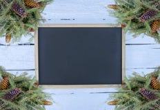 Julsammansättning med granfilialer och kottar på vit åldrades träbakgrund Festlig designmall för nytt år Inramat tomt arkivfoto