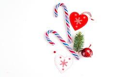 Julsammansättning med julgodisen, trädfilialer och att semestra prydnaden på vit bakgrund Lekmanna- lägenhet, bästa sikt arkivbilder