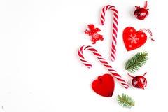 Julsammansättning med julgodisen, trädfilialer och att semestra prydnaden på vit bakgrund Lekmanna- lägenhet, bästa sikt arkivbild