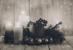 Julsammansättning med koppen, granbanch, stearinljus, klumpa ihop sig svart white Arkivbild