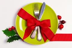 Julsammansättning med plattan, bestick, sörjer filialer, bandet och röda bär på den vita tabellen Vinterferier och festlig backg royaltyfri bild