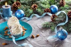 Julsammansättning med två muffin, stearinljus och feriegarneringar Royaltyfria Bilder