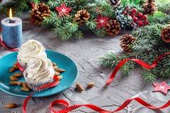 Julsammansättning med två muffin, stearinljus och feriegarneringar Arkivfoto