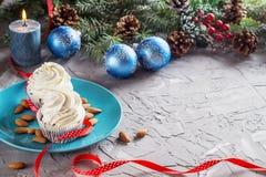 Julsammansättning med två muffin, stearinljus och feriegarneringar Arkivbild