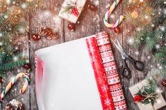 Julsammansättning med xmas som slår in, gran förgrena sig, gåvor, sörjer kottar, röda garneringar på träbakgrund royaltyfri bild