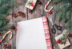 Julsammansättning med xmas som slår in, gran förgrena sig, gåvor, sörjer kottar, röda garneringar på träbakgrund royaltyfri fotografi