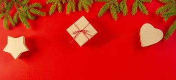 Julsammansättning på röd backgroud med granträdfilialer och närvarande gåvaaskar på röd bakgrund arkivfoton