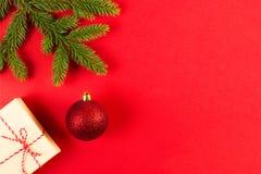 Julsammansättning på röd bakgrund Gröna granträdfilialer, Xmas-gåvaask och garnering Arkivfoto