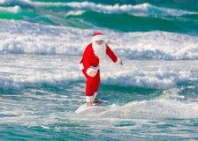 JulSanta Claus surfare som surfar med surfingbrädan på havet royaltyfri bild