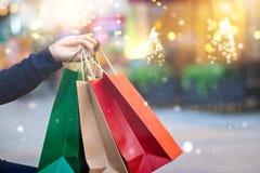 Julshopping-shopping påsar i hand med snöflingan royaltyfri foto