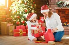 julskogen knurled morgon som snöig trails övervintrar wide den familjmodern och dottern packar upp, den öppna gåvan royaltyfria foton