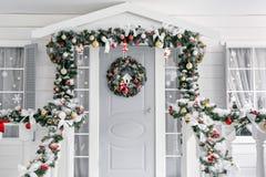 julskogen knurled morgon som snöig trails övervintrar wide farstubro ett litet hus med en dekorerad dörr med en julkrans träräkna Arkivfoto